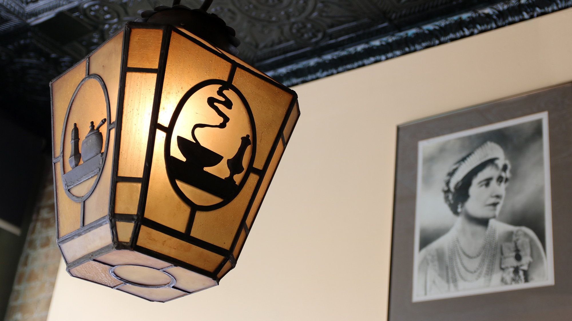 Antique café light hanging in front of one of the original photos of the Queen Mother that gave the restaurant its name