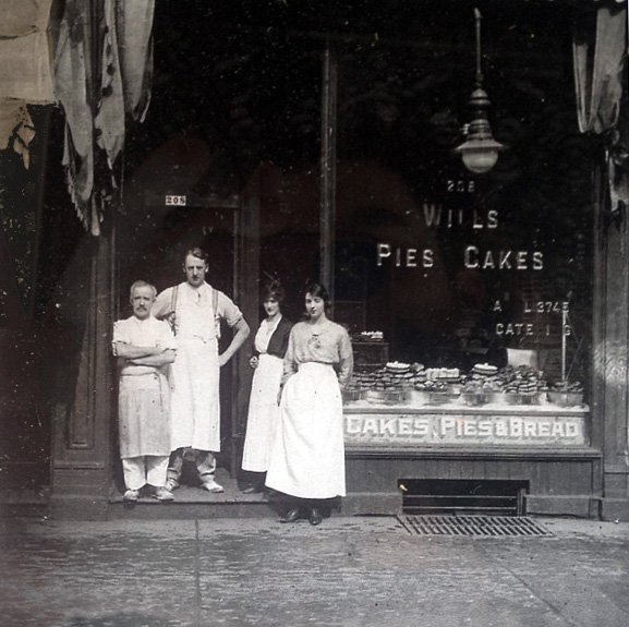 "Previous residents of 208 Queen St West standing outside the building. Window reads ""Wills Cakes, Pies & Bread""."